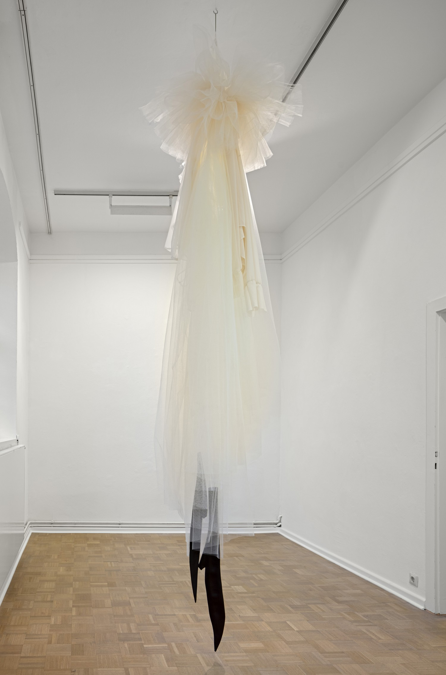 """Die Arbeit """"Loge"""" von Julie Béna besteht aus übergroßen, Raum einnehmenden Kleidungsstücken, die von der Decke herunterhängen und eine Irritation der Empfindung von Dimension und Raum auslösen."""