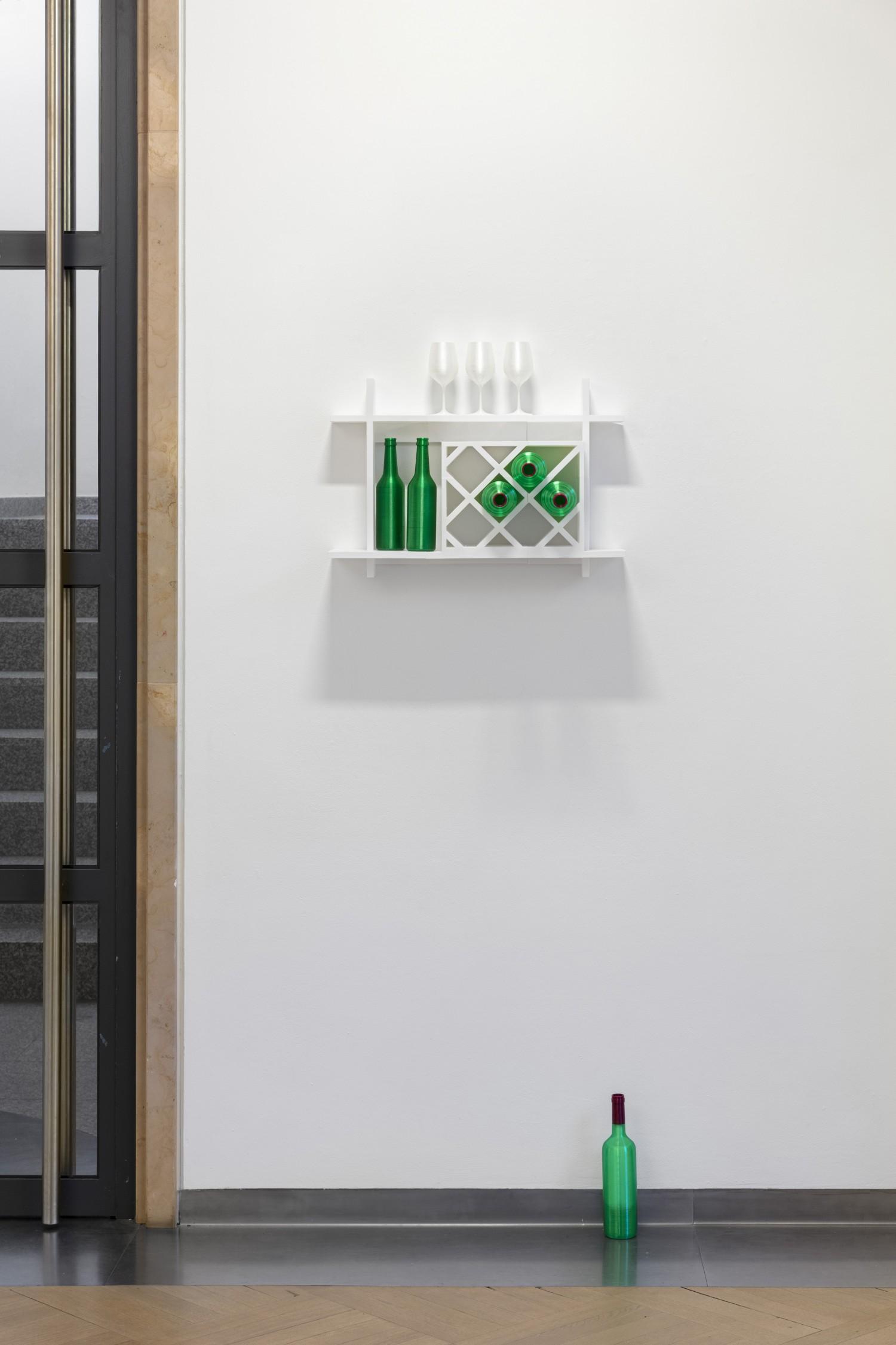 Ein 3D-gedrucktes weißes Wandregal, in dem 3D-gedruckte grüne Flaschen und weiße Gläser stehen. Eine Flasche steht unter dem Regal auf dem Boden.