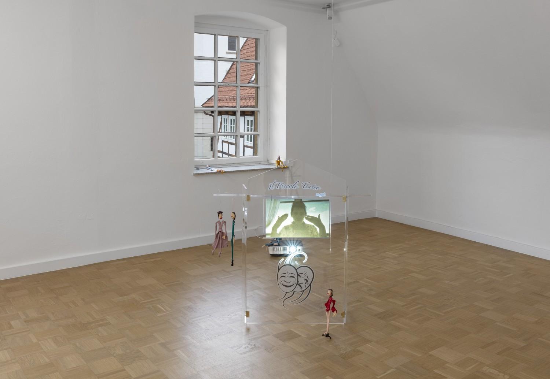 """Die Arbeit """"Il piccolo teatro"""" von Julie Béna stellt ein Puppentheater aus Plexiglas dar, das auf dem Boden steht. Auf das Objekt wird ein Video projiziert, das eine Handperformance der Künstlerin zeigt. Im Raum, um das Objekt herum, sind kleine Marionettenpuppen platziert."""