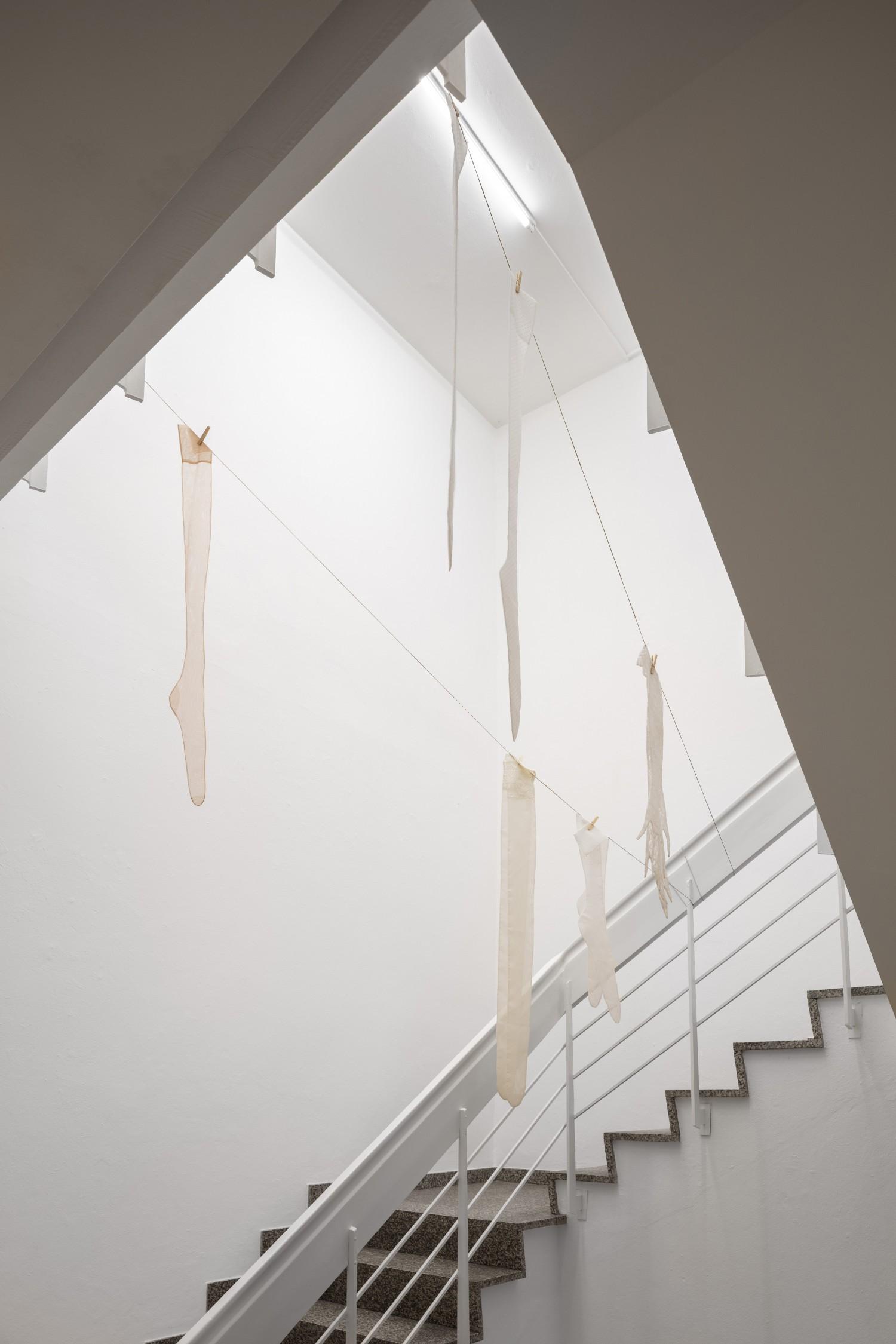 """Im Treppenhaus des Kunstvereins hängen sechs übergroße Seidenstrümpfe von einer Wäscheleine. Julie Béna schafft mit der Arbeit """"Le déshabillé"""" eine Irriation der Empfindung von Dimension und Raum."""