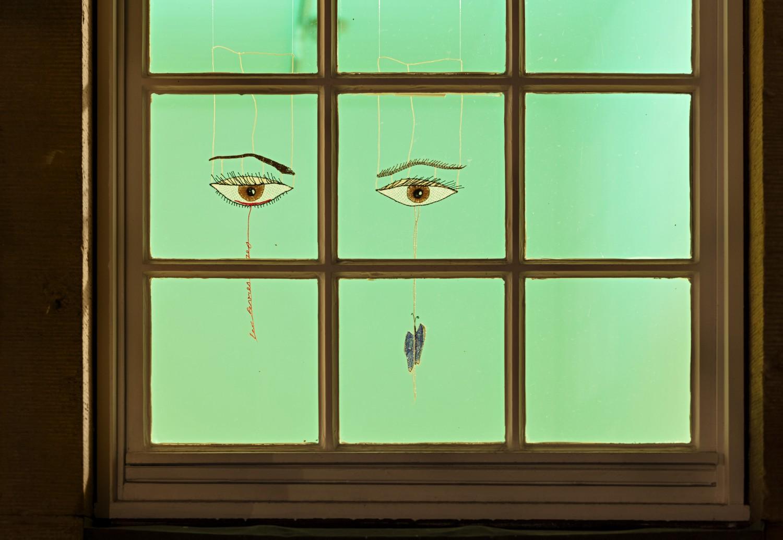 """Julie Béna greift in den aus handgeklöppelter Spitze gearbeiteten Objekten """"Les lèvres rouges –Eye"""" und """"Blue Butterfly –Eye-"""" den Titel der Ausstellung """"Les lèvres rouges"""" auf sowie das Motiv der Augen und des Schmetterlings. Die Objekte hängen vor dem Fenster und sind von außen zu erkennen."""