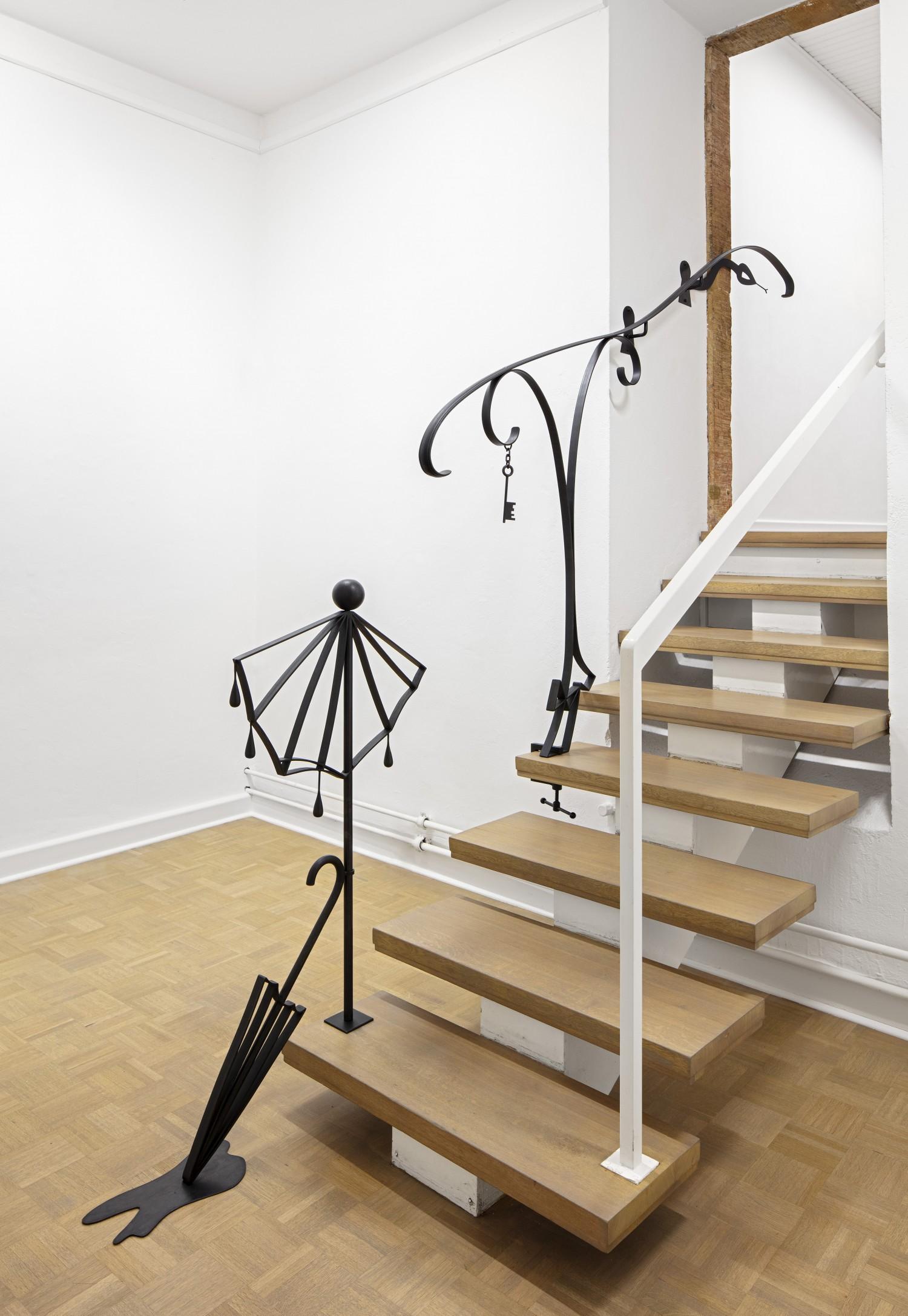 """Zwei Objekte der vierteiligen Werkreihe """"Ballustrade"""" von Julie Béna aus dem Jahr 2020, die aus schwarz beschichtetem Stahl bestehen. Die Objekte sind zum Teil auf der Treppe und zum Teil im Raum platziert. Den Objekten kommt Autonomie und Funktion gleichermaßen zu, sie sind Bild und tatsächlich Balustrade zugleich."""